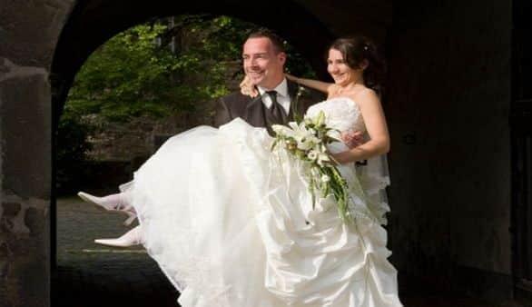 Braut wird über Türschwelle getragen